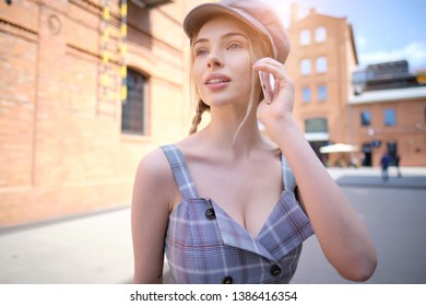 Cheerful woman talking on the phone in the street.