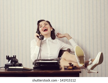 Cheerful woman talking on phone at desk