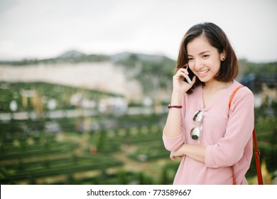 Cheerful woman talking on the phone on the street