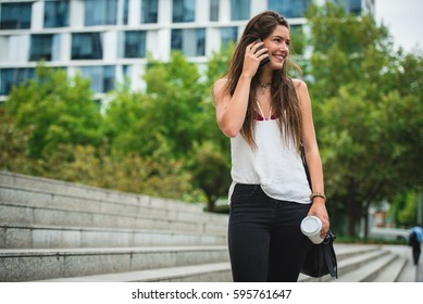 Cheerful woman talking phone and holding a paper cup on the stairs. Horizontal outdoors shot.