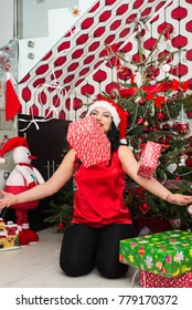 Cheerful woman throwing Christmas boxes gifts  in front of tree in her house