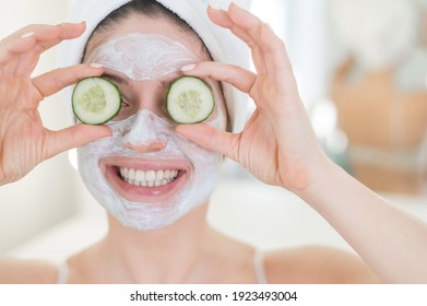 Cheerful woman with a towel on her hair and in a clay face mask and cucumbers on her eyes. Taking care of beauty at home