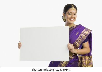 Cheerful woman in traditional Assamese mekhla holding a blank placard and smiling