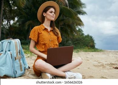 Cheerful woman traveler laptop vacation travel work beach