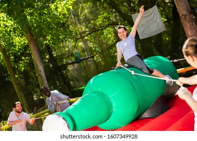 Cheerful woman trying to stay in saddle on inflatable rodeo bottle while her friends trying to fling her off
