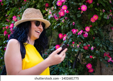 A Cheerful woman is using smarthphone in front of roses , she is typing a message or looking at social media