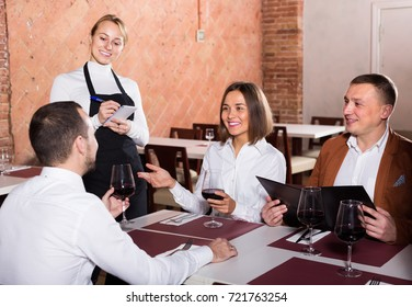 cheerful woman waiter receiving order from guests in country restaurant