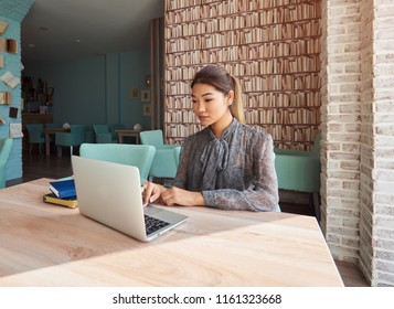 Cheerful woman watching  video on laptop computer while waiting for her order cafe, smiling hipster girl chatting with friends in network via net-book while relax in coffee shop