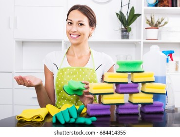 Cheerful woman wearing apron sitting with heap of cleaning sponges indoors