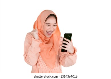 Cheerful woman wearing Muslim clothes while reading messages on her mobile phone, isolated on white background
