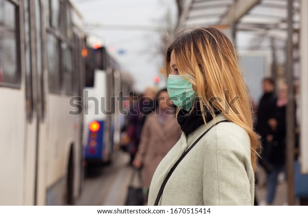 Cheerful woman wearing a sterile protective medical mask against coronavirus, Covid-2019 Asian pandemic sars virus at public bus station in European city street looking ahead, people on the background