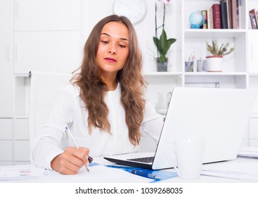 cheerful woman writing down information from computer at firm office