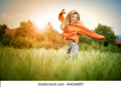 Cheerful woman. Young happy woman jumping with her arms up on a green grass lawn. Attractive woman cheering and enjoying the freedom on a sunny day. / Lifestyle