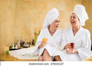 Cheerful women in bathrobes drinking juice: friends in spa salon