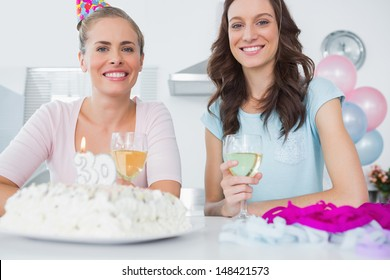 Cheerful women with birthday cake wearing party hats