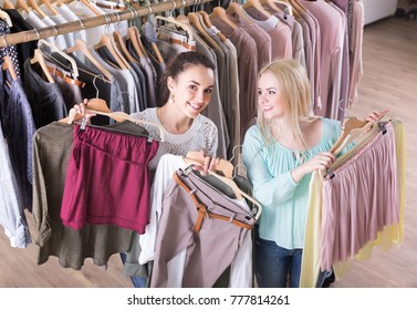 Cheerful women buying new garments at the store