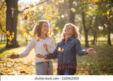 Cheerful women enjoying fall season in an autumn park