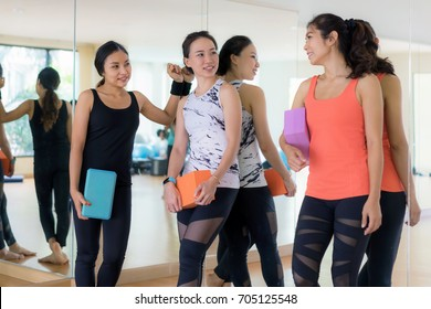 The cheerful women holding exercise blocks and smiling in fitness gym.