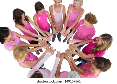 Cheerful women joined in a circle and looking at each other wearing pink for breast cancer on white background