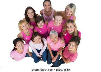 Cheerful women looking up wearing pink for breast cancer on white background
