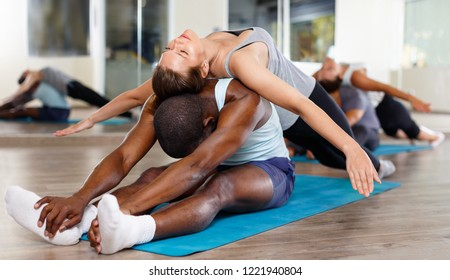 Cheerful women and men exercising in pairs during yoga class in modern fitness center
