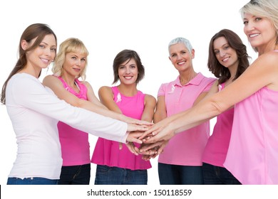 Cheerful women posing in circle holding hands looking at camera  wearing pink for breast cancer on white background