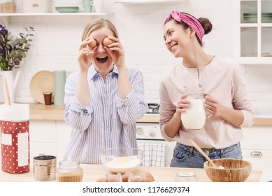 Cheerful women preparing breakfast together in the kitchen