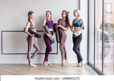 Cheerful women wearing activewear standing near large window hold yoga mats ready start fitness training and rejoice at meeting. The concept of sports lifestyle and like-minded people. Yoga concept