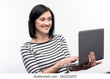 Cheerful worker. Beautiful dark-haired young woman in a striped pullover working on a laptop while standing isolated on a white background