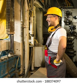 Cheerful worker in safety hat near machine on a factory