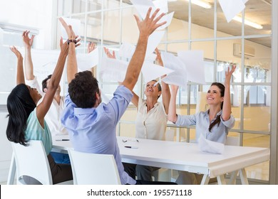 Cheerful workers throwing paper and smiling in the office