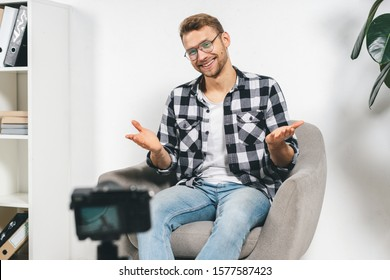 Cheerful young adult blogger smiling wide, gesturing, using broadcast equipment, recording online video for channel in social media, sitting against white wall background