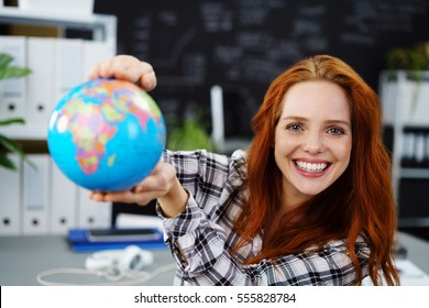 Cheerful young adult female in red hair holding globe in classroom. Obscured chalkboard behind her.