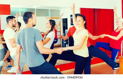 Cheerful young adults having active dance class. Selective focus