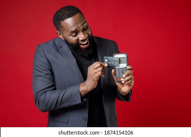 Cheerful young african american business man 20s in classic jacket suit hold wireless modern bank payment terminal to process acquire credit card payments isolated on red background studio portrait
