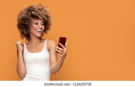 Cheerful young african american girl using mobile phone,smiling, posing on yellow background.