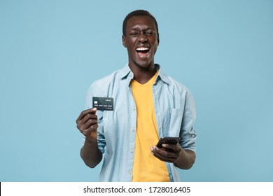 Cheerful young african american man guy in casual shirt, yellow t-shirt posing isolated on blue wall background. People lifestyle concept. Mock up copy space. Using mobile phone hold credit bank card