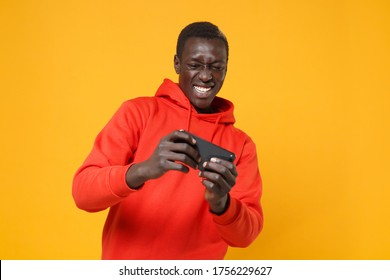 Cheerful young african american man guy in red streetwear hoodie posing isolated on yellow wall background studio portrait. People lifestyle concept. Mock up copy space. Play game with mobile phone