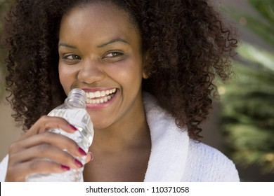 Cheerful young African American woman drinking mineral water