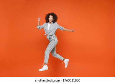 Cheerful young african american woman girl in gray casual clothes posing isolated on orange background studio portrait. People lifestyle concept. Mock up copy space. Jumping, spreading hands and legs