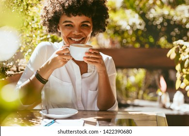 Cheerful young african woman with a cup of coffee sitting at cafe. Female having coffee at coffeeshop.