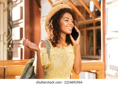 Cheerful young african woman in summer dress walking at the city, talking on mobile phone