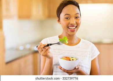 cheerful young afro american woman eating vegetable salad in home kitchen