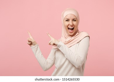 Cheerful young arabian muslim woman in hijab light clothes posing isolated on pink wall background in studio. People religious Islam lifestyle concept. Mock up copy space. Pointing index finger aside