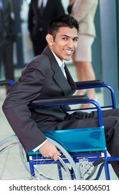 cheerful young Arabic handicapped businessman in office