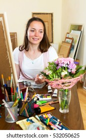 Cheerful young artist paints a picture at home