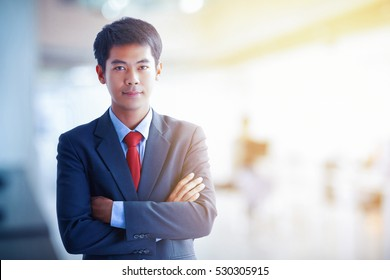 Cheerful young asian businessman in full suit keeping arms crossed and looking at camera in office