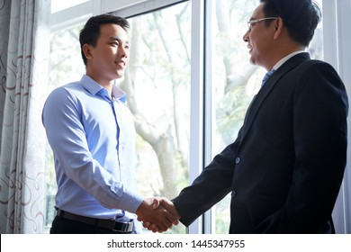 Cheerful young Asian businessman shaking hand of his mature coworker at meeting