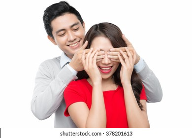 Cheerful young asian couple man and woman at home offering to each other gifts for lover's valentine day
