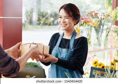 Fröhlicher junger asiatischer Florist, der Geschenkbox an den Kunden schenkt, bestellte sie online